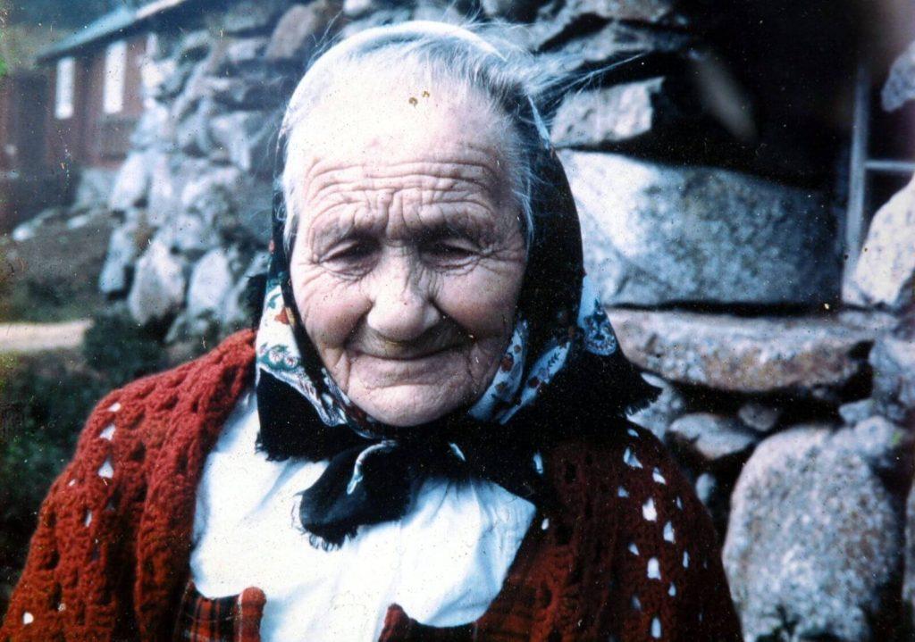 Gjendine Slålien in front of the stone building at Lake Gjende, where she was born in 1871.