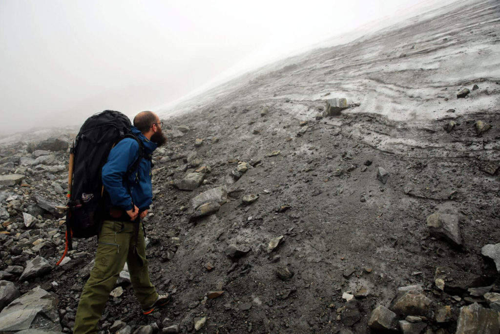 Julian looking at old, dirty and layered ice at the bottom of the northern ice patch at Storfonne.